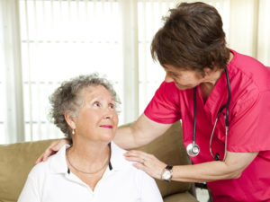 Nurse helps senior woman. Could either be in-home care or at a nursing home or assisted living facility.